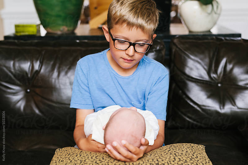 big brother admiring his new baby brother by Kelly Knox for Stocksy United