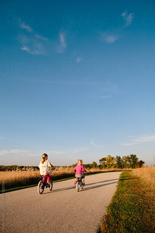 two sisters ride bikes down path by Brian Powell for Stocksy United