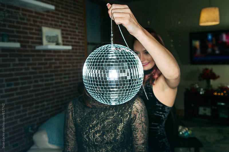 NYE: Friend Holds Mirror Ball In Front Of Girl's Face by Sean Locke for Stocksy United