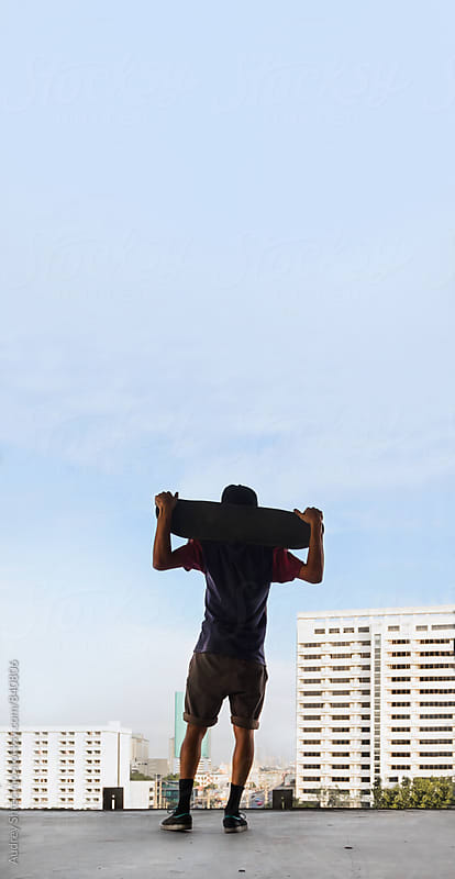 Skateboarder looking on cityscape holiding his board/look from behind. by Marko Milanovic for Stocksy United