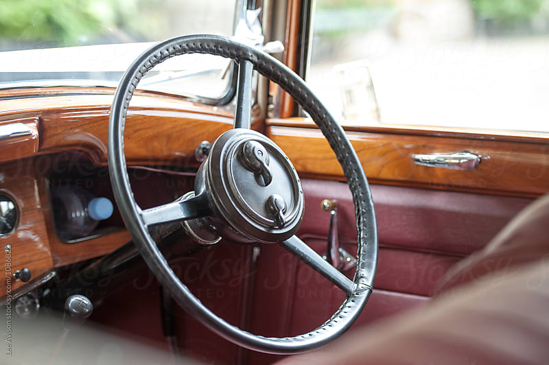 steering wheel and wood and leather interior of a vintage car by Lee Avison for Stocksy United