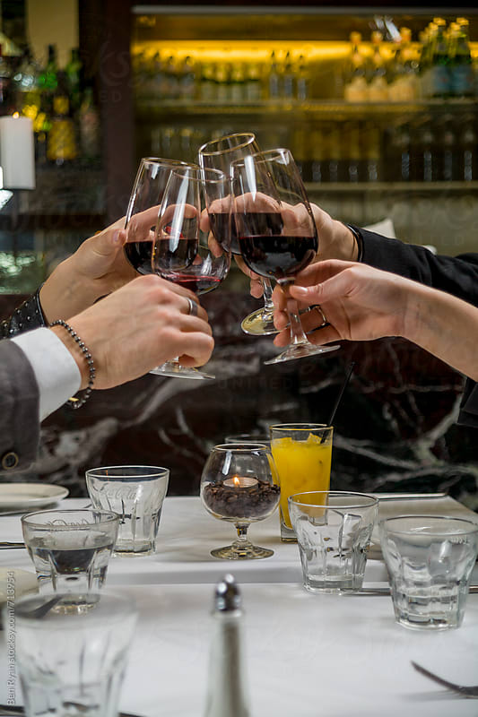 Four friends toasting with wine at high class restaurant by Ben Ryan for Stocksy United