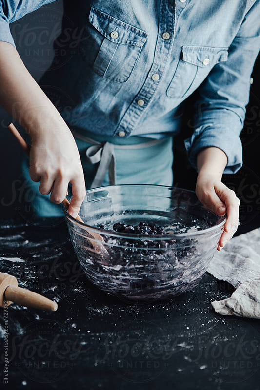 Woman mixing blueberry pie filling by Ellie Baygulov for Stocksy United