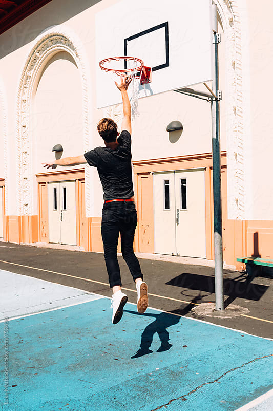 Man Wearing White High Top Converse Jumping To Touch Hoop On Blue Basketball Court by Luke Mattson for Stocksy United