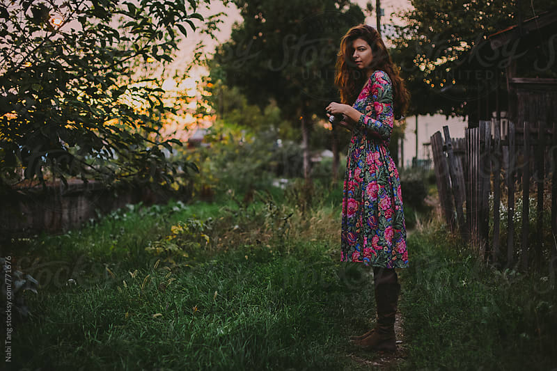 Beautiful young woman in floral dress with camera in the garden by Nabi Tang for Stocksy United