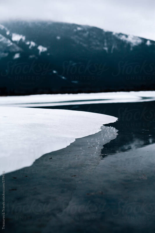 Frozen lake early in the morning with mountains by Treasures & Travels for Stocksy United