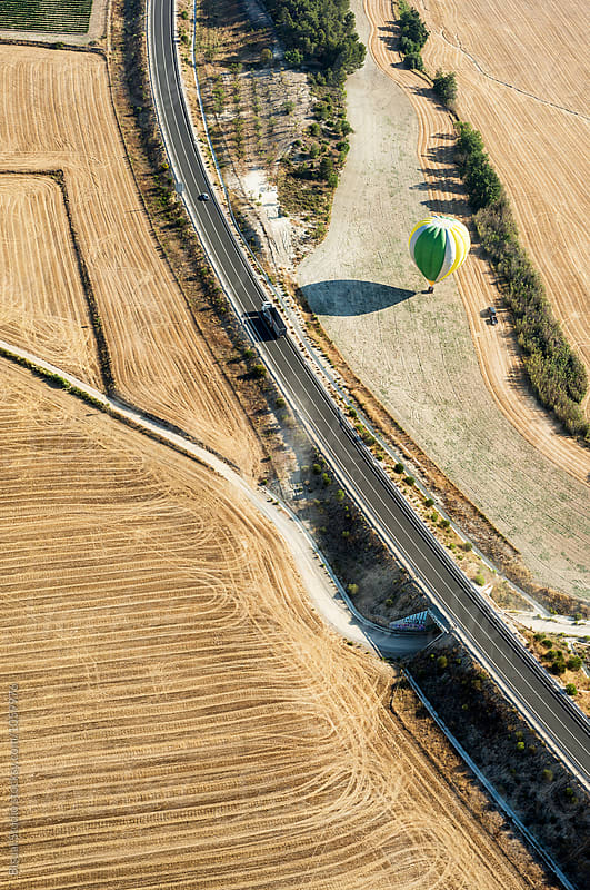 Hot air balloon landing on a wheat field,Igualada, Spain by Bisual Studio for Stocksy United