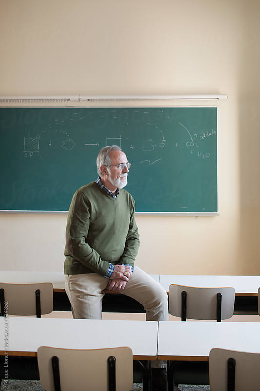 Portrait of a mature professor in a classroom with green blackboard by Miquel Llonch for Stocksy United