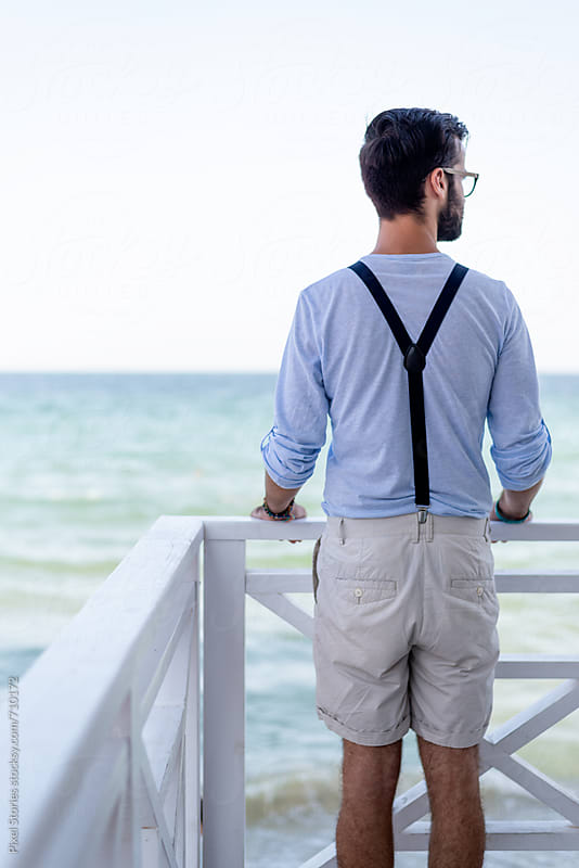 Young man staring at the sea by Pixel Stories for Stocksy United