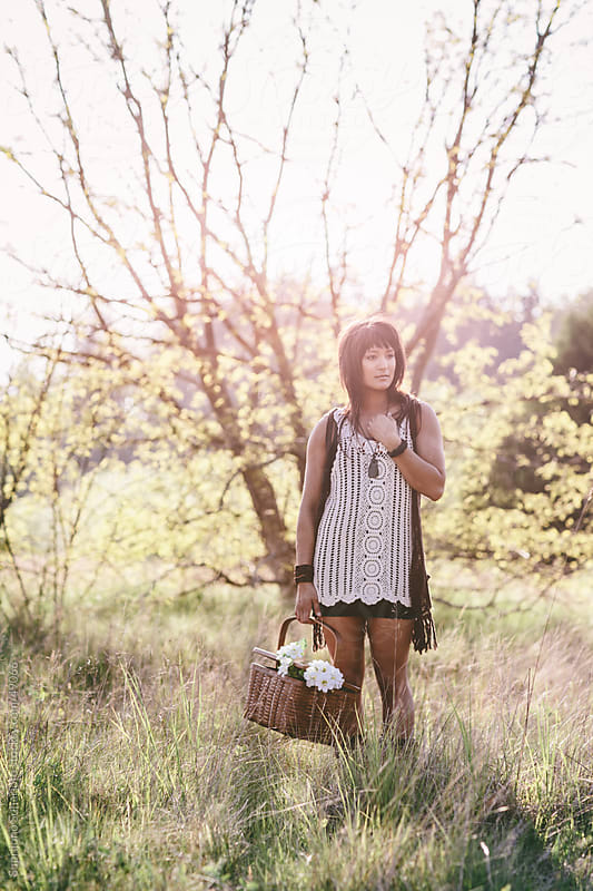 Beautiful woman carrying flowers and a picnic basket on a grass  by Suprijono Suharjoto for Stocksy United