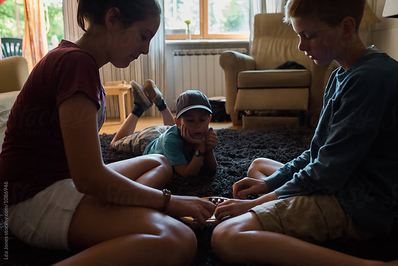 children playing a game at home by Léa Jones for Stocksy United