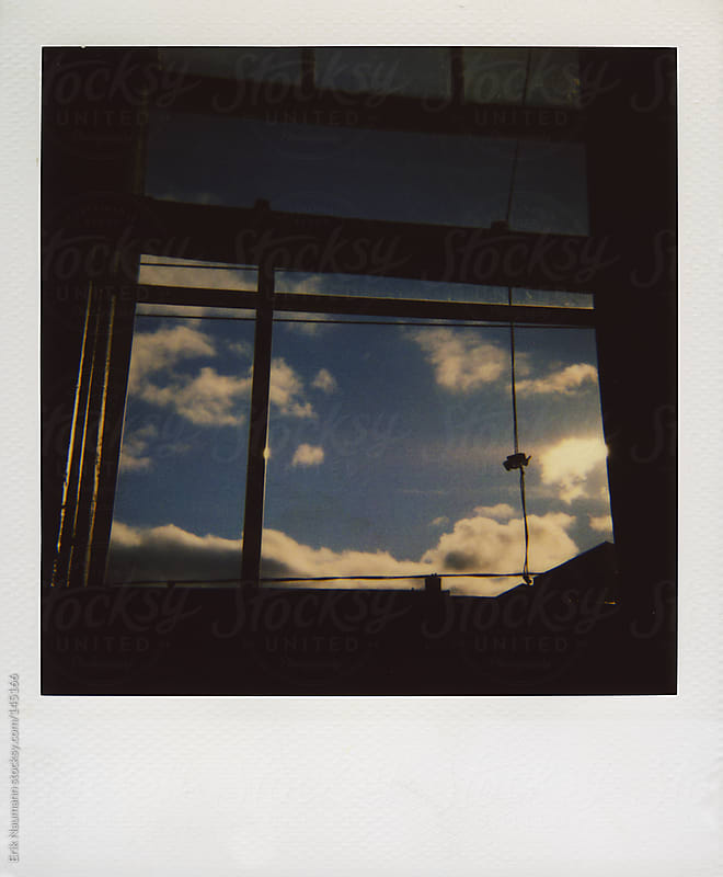Polaroid view of the sky from a window by Erik Naumann for Stocksy United