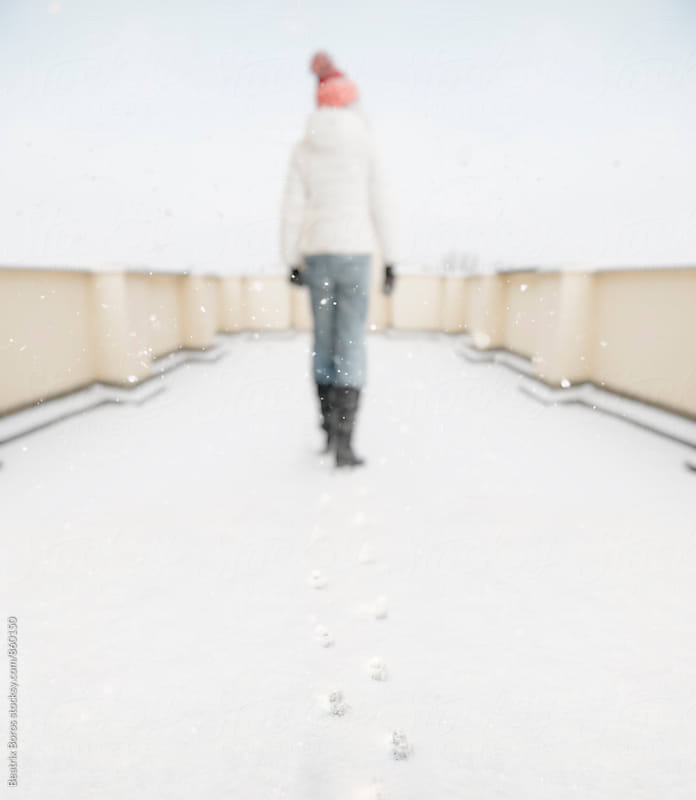 Woman walks away in the snow, only het footmarks remain by Beatrix Boros for Stocksy United