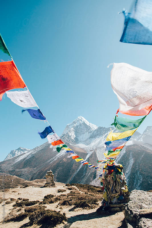Closeup of Buddhist prayer flags blowing in the wind from a stupa high in the Himalaya mountains. by Soren Egeberg for Stocksy United