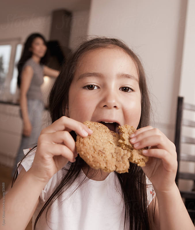 Young Girl Eating Cookie by Tyler Olson for Stocksy United