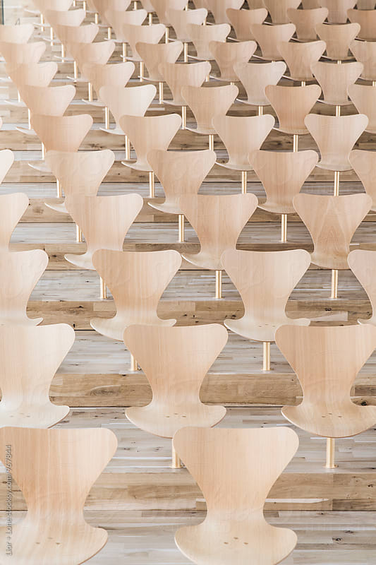 Diagonal symmetrical rows of designer wooden chairs by Lior + Lone for Stocksy United