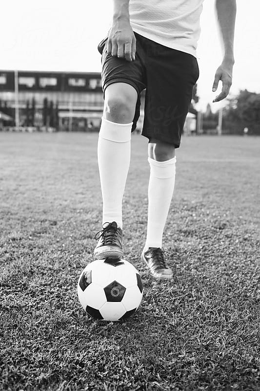 Boy in football boots and socks standing on soccer ball by Ani Dimi for Stocksy United