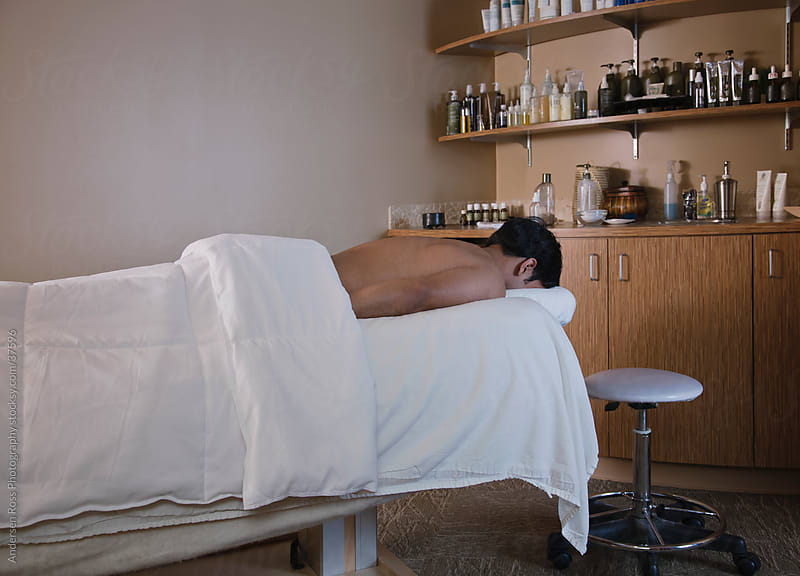 Man lying on massage table by Andersen Ross Photography for Stocksy United