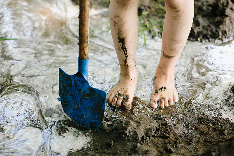 girl plays in the mud with shovel by Brian Powell for Stocksy United