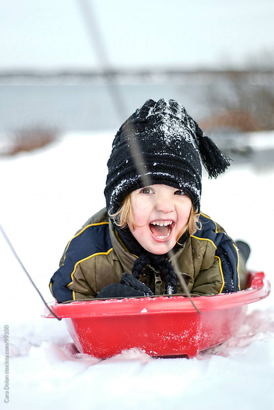 Child laughs joyfully while being pulled on a red sled in winter by Cara Dolan for Stocksy United