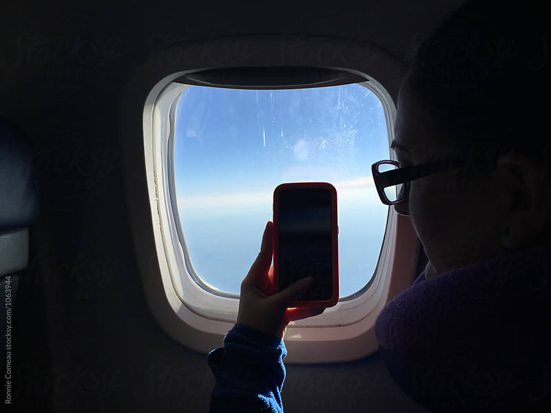 Woman Taking Cell Phone Picture Out Of Airplane Window by Ronnie Comeau for Stocksy United