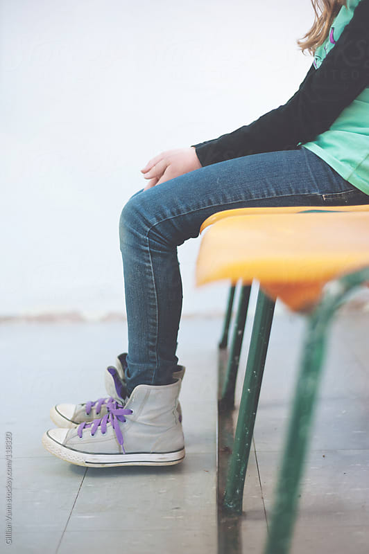 teen girl sitting on plastic chairs, waiting by Gillian Vann for Stocksy United