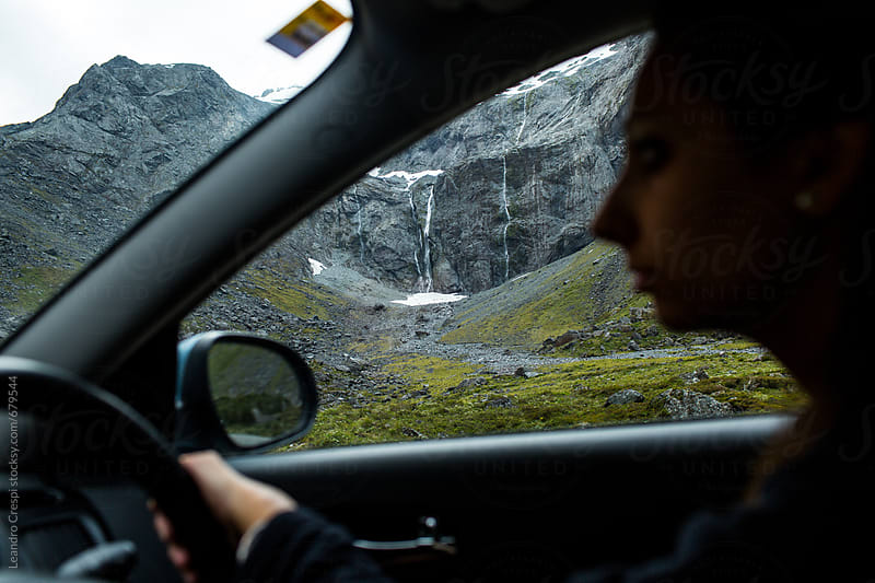 Woman driving a car through a valley by Leandro Crespi for Stocksy United