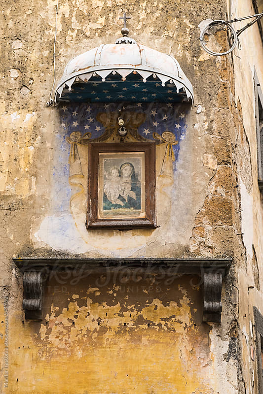 Painting of Madonna and Child hanging on a facade by Marilar Irastorza for Stocksy United