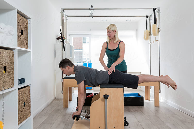 Pilates stretching exercise performed on the Wunda Chair with guidance from an instructor by Paul Phillips for Stocksy United