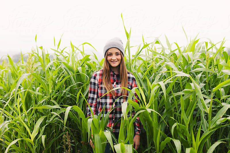 Smiling teen girl standing in a corn fields.  by BONNINSTUDIO for Stocksy United