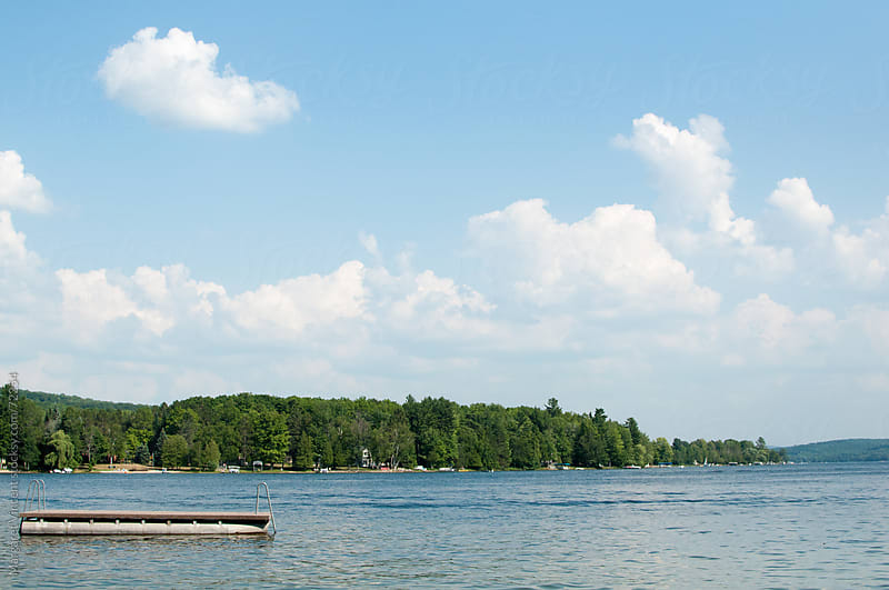 a swim raft floats on a freshwater lake by Margaret Vincent for Stocksy United
