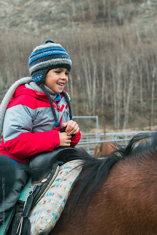 a happy child riding horseback by Tara Romasanta for Stocksy United