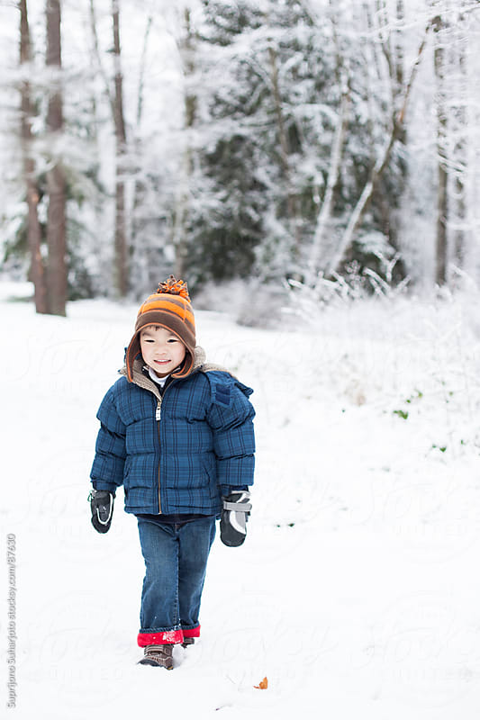 Asian boy walking in the snow during winter by Suprijono Suharjoto for Stocksy United