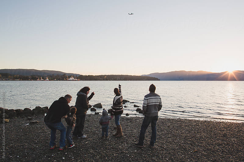 Multigenerational family at beach looking at airplane by Rob and Julia Campbell for Stocksy United