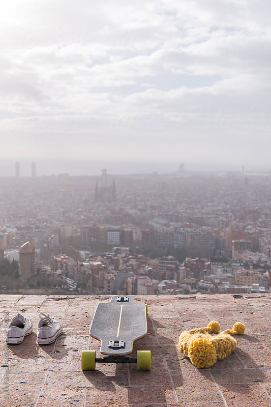Skate,shoes and hat against of Barcelona cityscape by Guille Faingold for Stocksy United