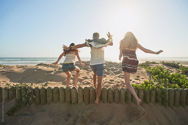 Three Friends running towards the Beach by Aila Images for Stocksy United
