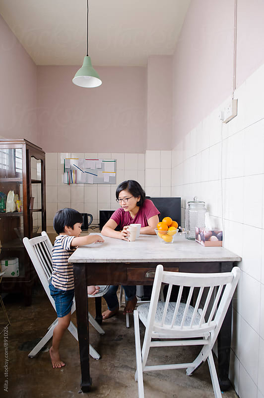 Mother and son having conversation in the pantry by Alita Ong for Stocksy United