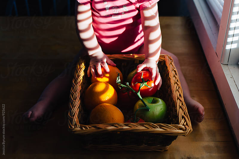 Toddler playing with fruit in basket on table by Jessica Byrum for Stocksy United