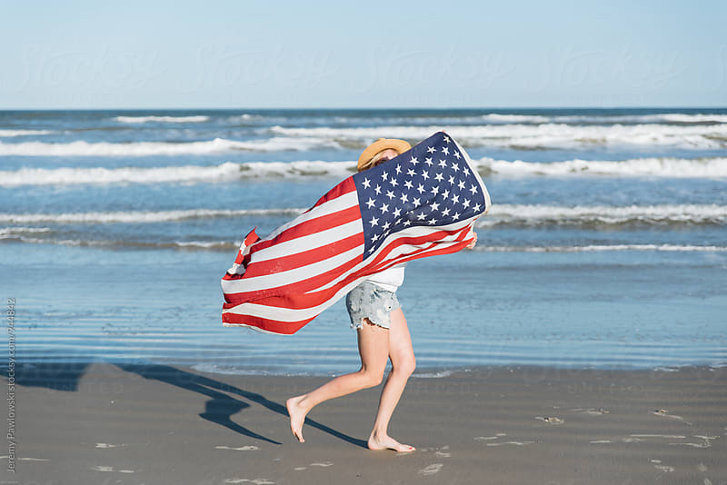 Woman running down beach with American Flag. Ocean in background. by Jeremy Pawlowski for Stocksy United