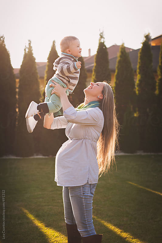 Cute toddler boy lifted in the air by his beautiful pregnant mother by Lea Csontos for Stocksy United