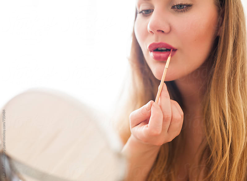 Woman applying lipstick on lips by Jacob Lund for Stocksy United