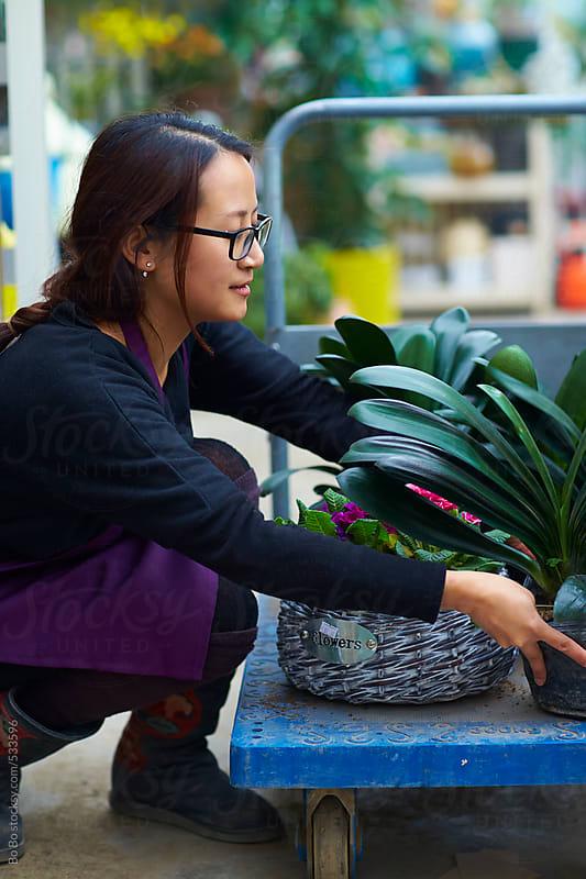 female florist in shop by Bo Bo for Stocksy United