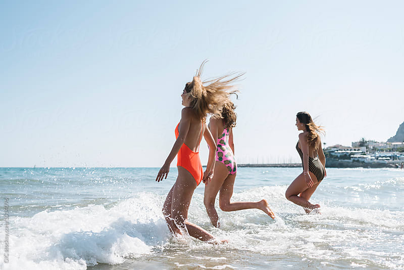 Three girls running in the sea by Simone Becchetti for Stocksy United