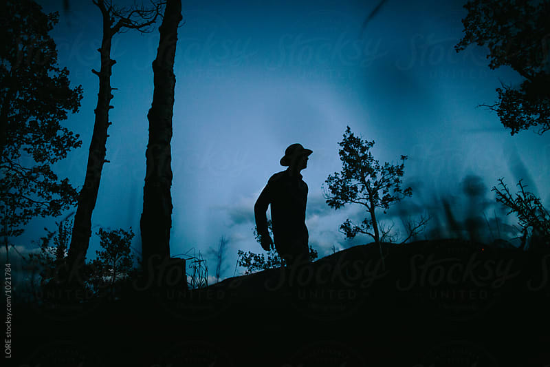 one adult male walks at dusk in the forest by LORE for Stocksy United