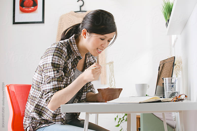Casual chinese woman eating noodles and working on a laptop at home. by BONNINSTUDIO for Stocksy United