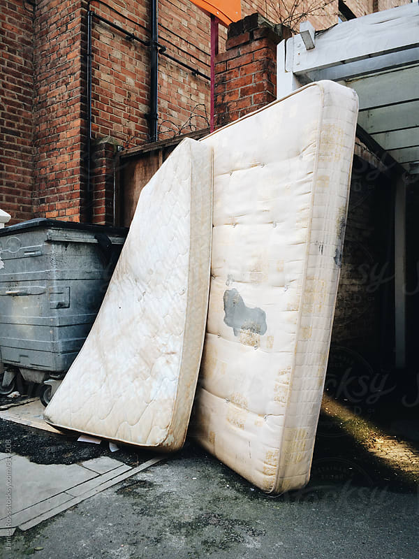 Two mattresses left in the street by James Ross for Stocksy United
