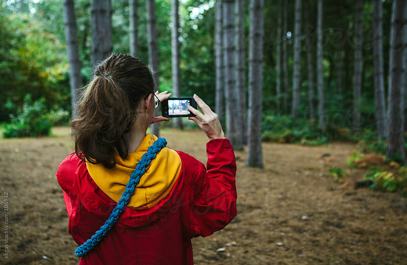 Woman taking a picture in a wood by kkgas for Stocksy United