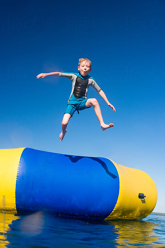 Boy Jumping Into Summer Lake From Water Trampoline At Cottage on Sunny Summer Day by JP Danko for Stocksy United