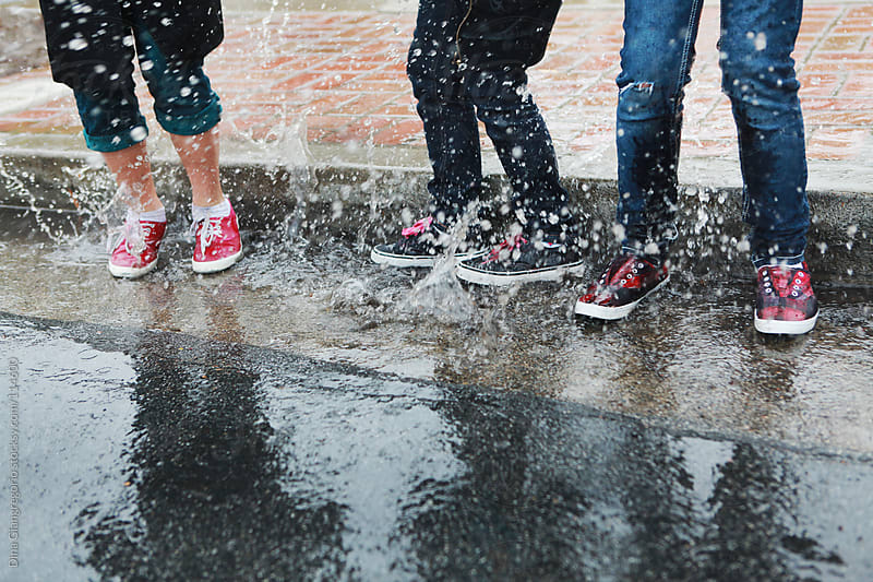 Three kids playing in the rain showing water splashing by Dina Giangregorio for Stocksy United