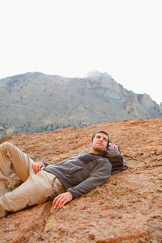 Young man rest on rock cliff at sunrise by Linzy Slusher for Stocksy United